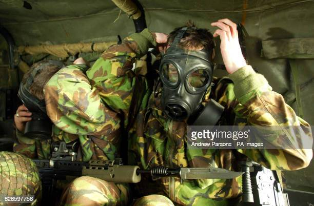 Private Charlie Curnow holding a SA80A2 with Private Neil Clish holding a GPMG from 3rd Battalion practice wearing gas masks at a press day near...