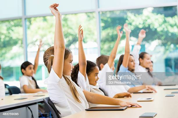 Private elementary school students raising hands to answer teacher's question