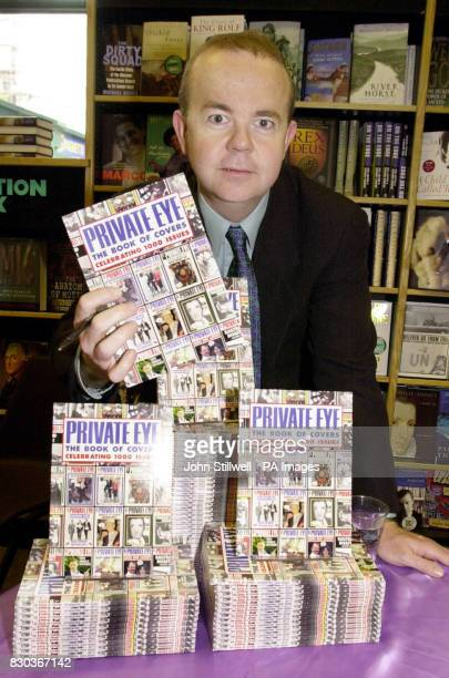 Private Eye editor Ian Hislop also of television's Have I Got News For You news quiz holds a copy of the book of front covers celebrating 1000 issues...