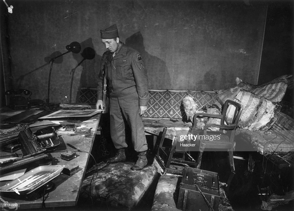 Private First Class Richard Blust of Michigan surveys the bunker at the German Reichschancellery in Berlin where Adolf Hitler and his wife Eva Braun are thought to have committed suicide. A fire has destroyed much of the room's contents.