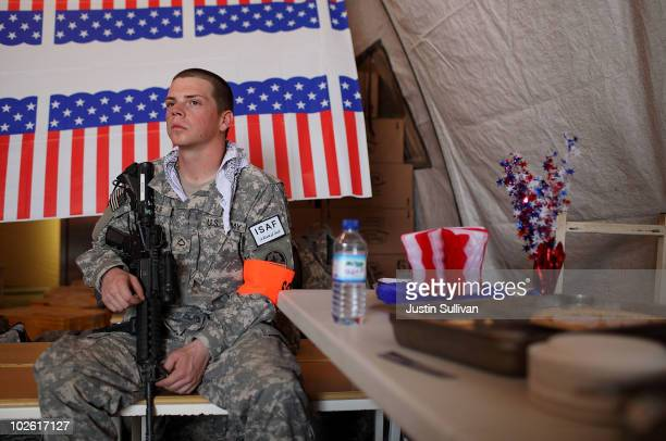 S Private First Class Thomas Baur provides security in a tent with tables of desserts during an Independence Day BBQ for troops at Kandahar Airfield...