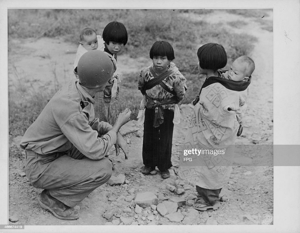 US Private Henry W Arsenault offering candy to Japanese children as the children carry their younger siblings on their backs World War Two Kyushu...