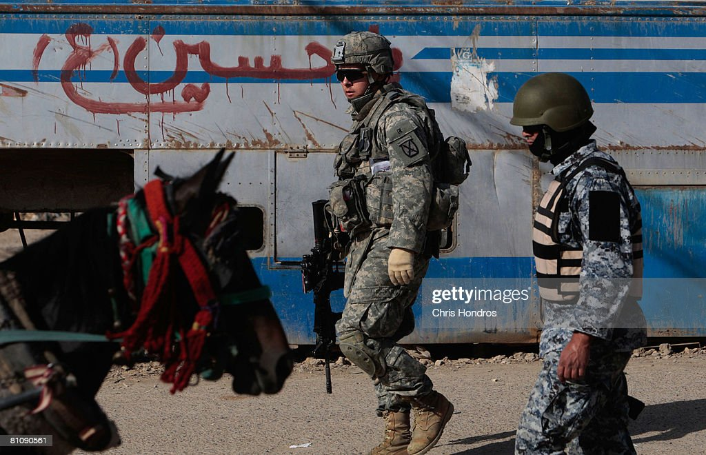 Private Joshua Fury Guerrero of Melbourne,Florida (center) of the 2nd Battalion, 30th Infantry Regiment of the 10th Mountain Division patrols alongside an Iraqi National Police member (R) while a horse drawing a cart rides by during a daytime joint patrol in Baladiyat neighborhood May 15, 2008 in Baghdad, Iraq. 10th Mountain soldiers take daily joint patrols with the Iraqi National Police, in the ongoing effort to build up stable national Iraqi security institutions aligned with the national government.