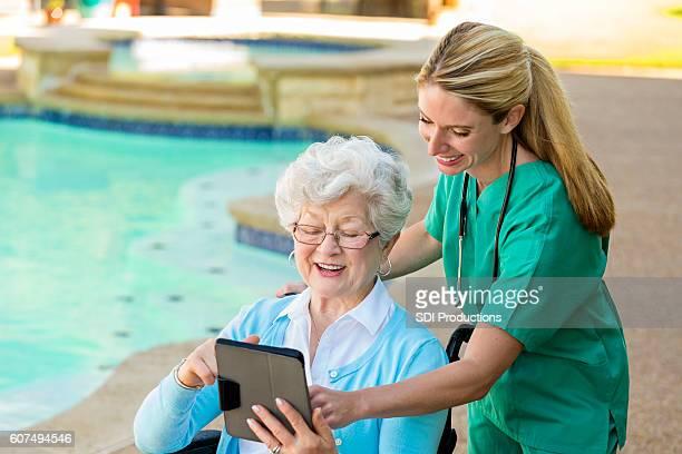 Private nurse helps senior patient use digital tablet