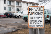 old, rusty private parking sign stating unauthorized vehicles will be towed at owners expense.