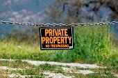 black orange white private property hanging sign