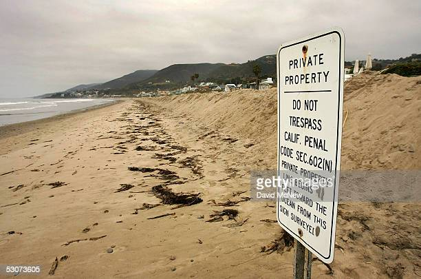 A private property sign stands between the public beach and piles of sand that have been pushed onto exclusive beachfront properties from the beach...