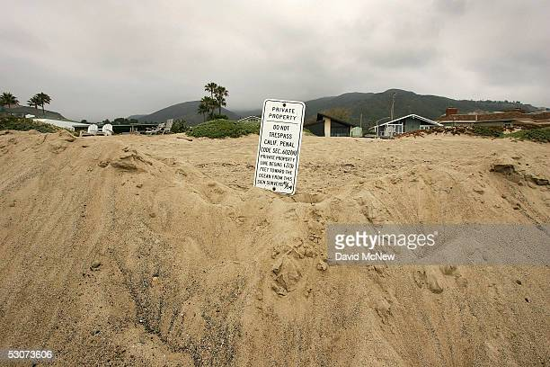 A private property sign stands on piles of sand that have recently been pushed onto exclusive beachfront properties from the public beach on June 15...