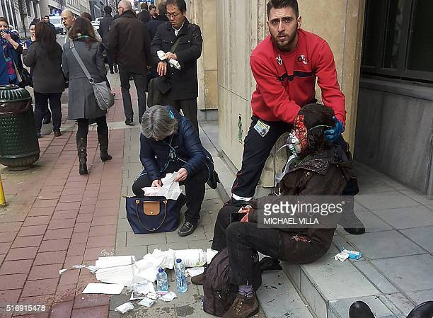TOPSHOT A private security guard helps a wounded women outside the Maalbeek Maelbeek metro station in Brussels on March 22 2016 after a blast at this...