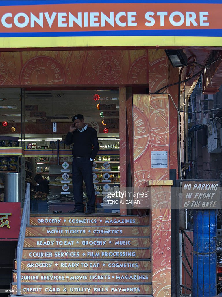 A private security guard talks on his mobile phone at the entrance of a grocery store in New Delhi on December 8, 2012. India's minority government narrowly won a final vote in parliament December 7 for its controversial move to allow in foreign supermarkets, giving a boost to its reform agenda.
