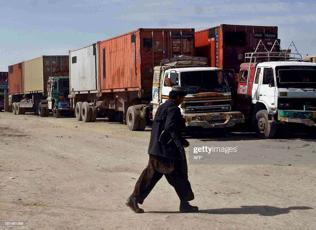 A private security personal walks past NATO supply trucks parked at the NLC terminal after crossing the Afghanistan border in Chaman on February 11, 2013. The US military has started to withdraw equipment from Afghanistan through Pakistan ahead of next year's deadline for combat troops to leave the war against the Taliban. AFP PHOTO / Asghar ACHAKZAI