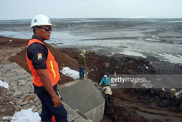 A private security personnel guards a section of the protective wall as workers place reinforcements against a sea of mud from the mud volcano in...