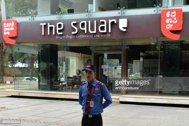 A private security personnel stands guard in front of Cafe Coffee Day Square outlet situated in the Cafe Coffee Day Head Office building which was...