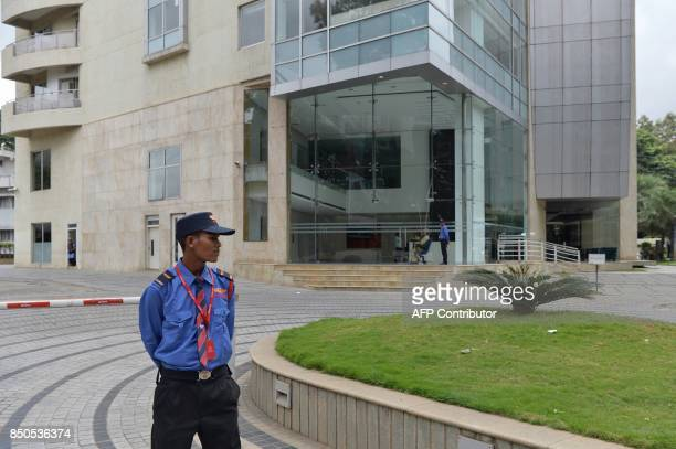 A private security personnel stands guard in front of Cafe Coffee Day Head Office building which was raided by the Income Tax Department in Bangalore...