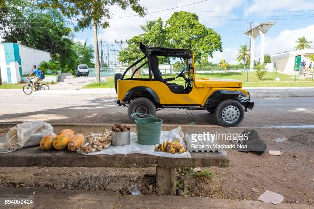 Private small business selling fruit and vegetables in the sidewalk Small yellow jeep parked along broken down sidewalk