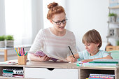Private female tutor helping young student with homework at desk in bright child's room