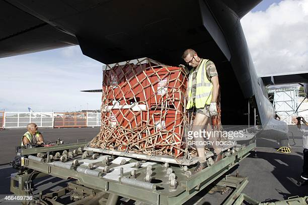 Privates load relief equiment into a French Army logistical transport plane bound for Vanuatu transporting food water and relief at the French Aerial...