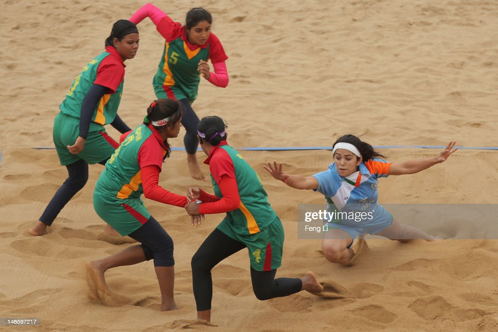 Priyanka Negi (R) of India is tackled as she competes during the Beach Kabaddi Women's Team Group A match between India and Bangladesh on Day 4 of the 3rd Asian Beach Games Haiyang 2012 at Fengxiang Beach on June 20, 2012 in Haiyang, China.