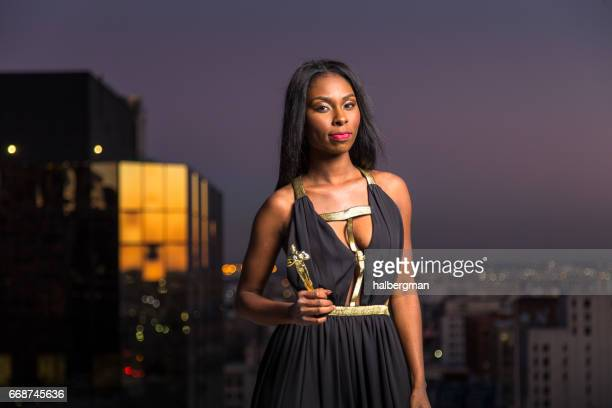 Prizewinning Woman Standing on Urban Rooftop with Award