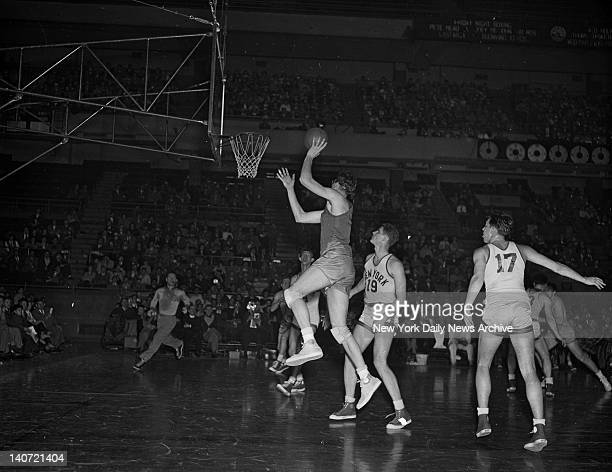 Pro basketball's George Mikan pushes the ball unerringly toward the basket for another two points while helpless Lee Knorek of the New York Knicks...