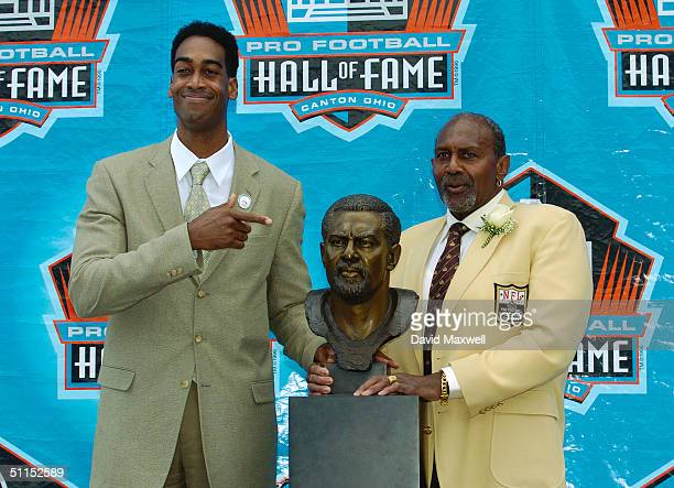 Pro Football Hall of Fame enshrinee Bob Brown and his son and presenter Robert Brown pose with Bob's bust during the 2004 NFL Hall of Fame...