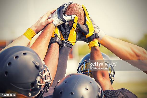 Pro football players holding ball in huddle