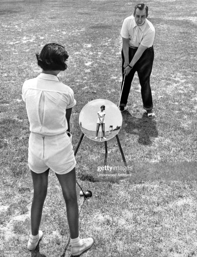 Pro golfer Homer Herpel teaches a student with a technique that he developed, St. Louis, Missouri, May 1, 1951. He learned to swing left handed so that by using a mirror, his students could compare their swing to his perfect form.