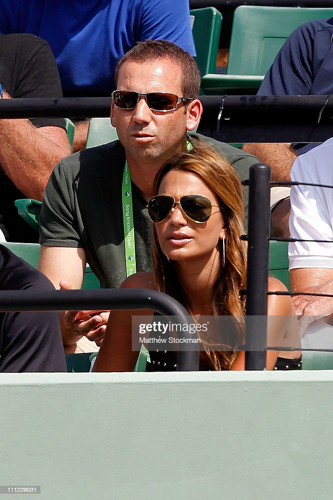 Pro golfer Sergio Garcia (top) and Stacey Gardner, the wife of tennis player Mardy Fish, watch Fish's match against David Ferrer of Spain during the Sony Ericsson Open at Crandon Park Tennis Center on March 30, 2011 in Key Biscayne, Florida.
