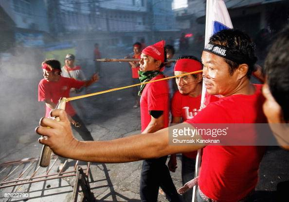 Pro government supporters uses a sling against antigovernment protesters during a demonstration near early morning outside Government House on...