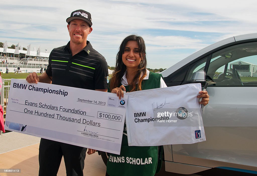 PGA TOUR pro <a gi-track='captionPersonalityLinkClicked' href=/galleries/search?phrase=Hunter+Mahan&family=editorial&specificpeople=885292 ng-click='$event.stopPropagation()'>Hunter Mahan</a> presents a $100,000 Evans Scholarship donation and a signed pin flag to Scholar Yesenia Juarez at the 2013 BMW Championship on September 14, 2013 in Lake Forest, Illinois. BMW made the donation in Mahan's name because he was the first to hit a hole-in-one at the 2013 BMW Championship.