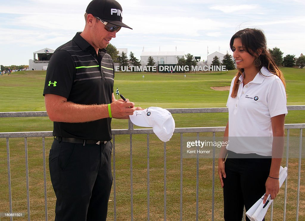PGA TOUR pro <a gi-track='captionPersonalityLinkClicked' href=/galleries/search?phrase=Hunter+Mahan&family=editorial&specificpeople=885292 ng-click='$event.stopPropagation()'>Hunter Mahan</a> signs a BMW Championship hat for Evans Scholar Yesenia Juarez at the 2013 BMW Championship on September 14, 2013 in Lake Forest, Illinois. BMW made a $100,000 donation to the Evans Scholars Foundation in Mahan's name because he was the first to hit a hole-in-one at the 2013 BMW Championship.