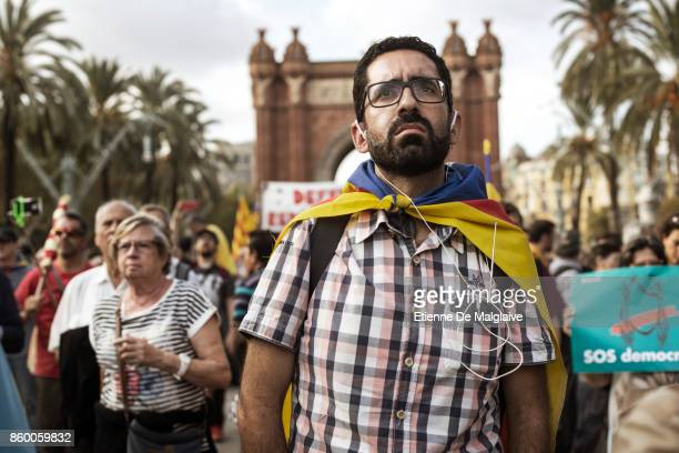 Pro independence supporters arrive to watch Catalan President Carles Puigdemont on big screens outside the Parliament of Catalunya announce that he...