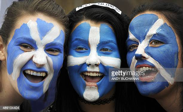 Pro Independence supporters pose with their faces painted with St Andrew's Cross during a rally in George Square in Glasgow Scotland on September 19...