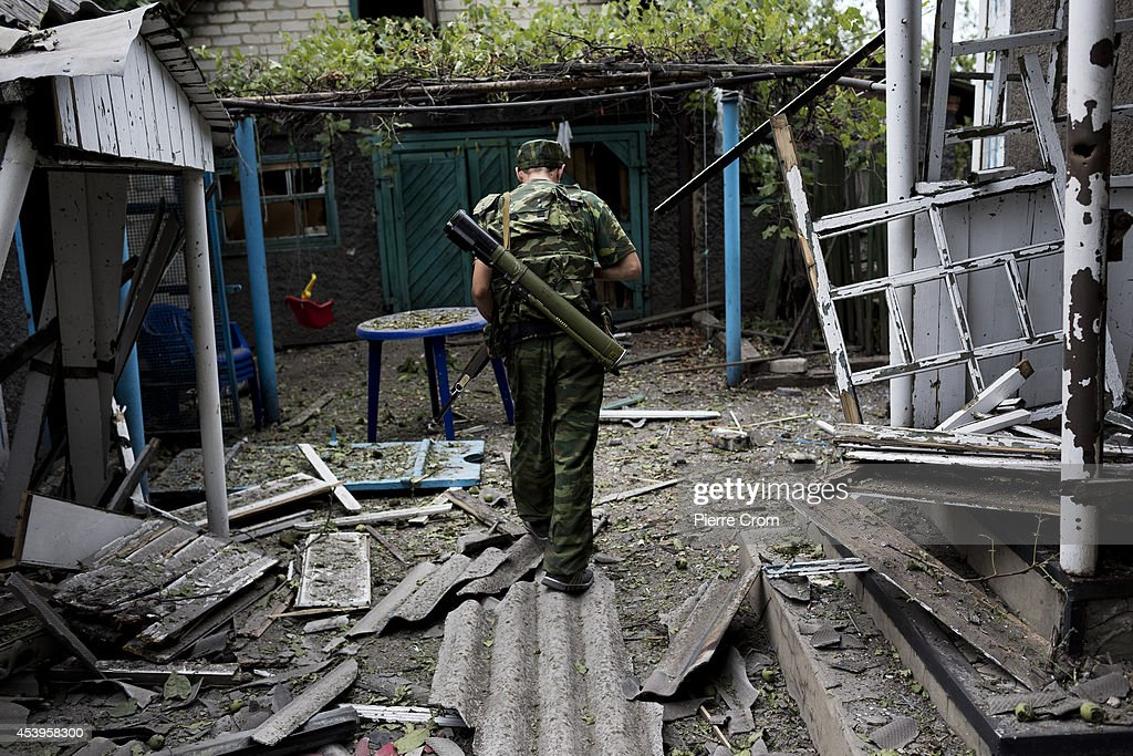 A pro Russian rebel walks through a garden in the Staromykhailivka quarter after it was hit by an artillery shell, on August 22, 2014 in Donetsk, Ukraine. In the last week several neighborhoods in the Pro-Russian rebel-held city of Donetsk have been bombarded with sustained artillery fire from Ukrainian troops as fighting on the city's outskirts has become more intense.