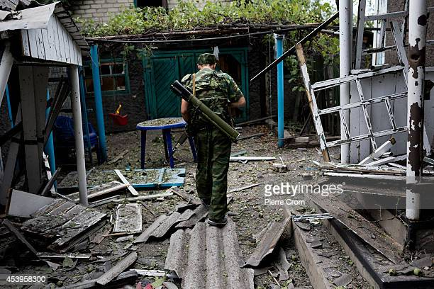 A pro Russian rebel walks through a garden in the Staromykhailivka quarter after it was hit by an artillery shell on August 22 2014 in Donetsk...