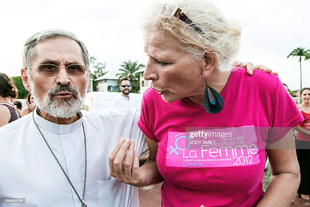 A pro same-sex marriage protester speaks with bishop Emmanuel Lafont (L) during a protest against plans to legalise same-sex marriage in Cayenne, in French Guiana, on January 12, 2013. Tens of thousands are set to march in Paris to denounce government plans to legalise same-sex marriage and adoption which have angered many Catholics and Muslims, France's two main faiths. The French parliament is to debate the bill -- one of the key electoral pledges of Socialist President at the end of this month.