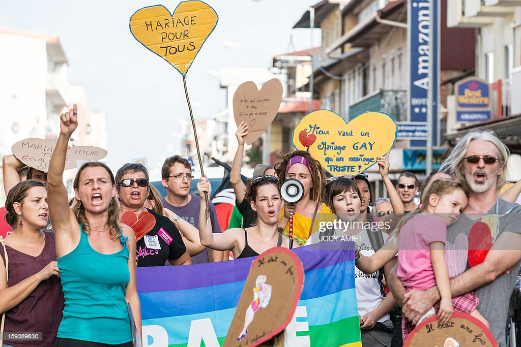 Pro same-sex marriage protesters shout slogans and hold placards during a counter-demonstration of a march against plans to legalise same-sex wedding in Cayenne, in French Guiana, on January 12, 2013. Tens of thousands are set to march in Paris to denounce government plans to legalise same-sex marriage and adoption which have angered many Catholics and Muslims, France's two main faiths. The French parliament is to debate the bill -- one of the key electoral pledges of Socialist President at the end of this month. AFP PHOTO JODY AMIET
