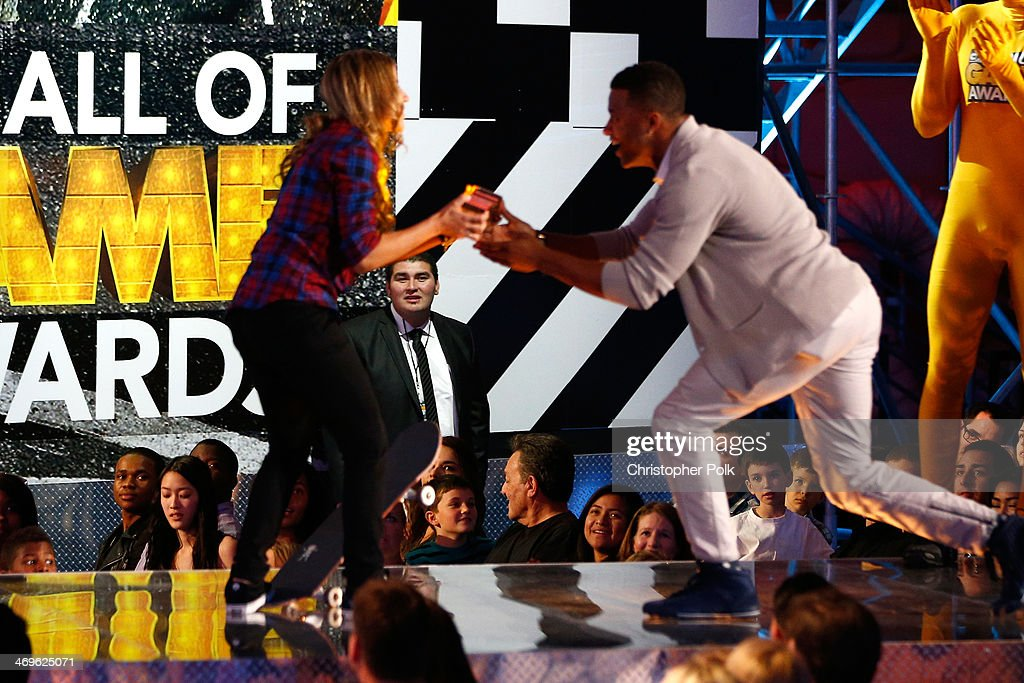 Pro skateboarder Leticia Bufoni (L) accepts the She Got Game award from presenter Randall Cobb onstage during Cartoon Network's fourth annual Hall of Game Awards at Barker Hangar on February 15, 2014 in Santa Monica, California.