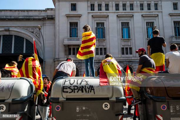 Pro unionist seen standing on a trash container that say 'Fuck Spain' A large number of citizens protested on Sunday in Barcelona against the...