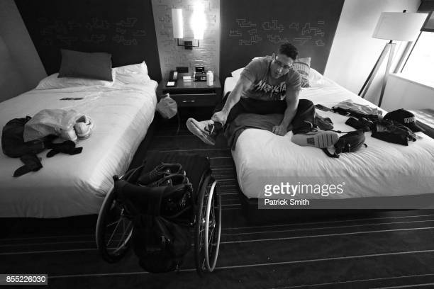 Pro Wheelchair Bodybuilder Johnny Quinn gets off his bed after getting dressed in his hotel room prior the Dallas Europa Games Get Fit Sports Expo...