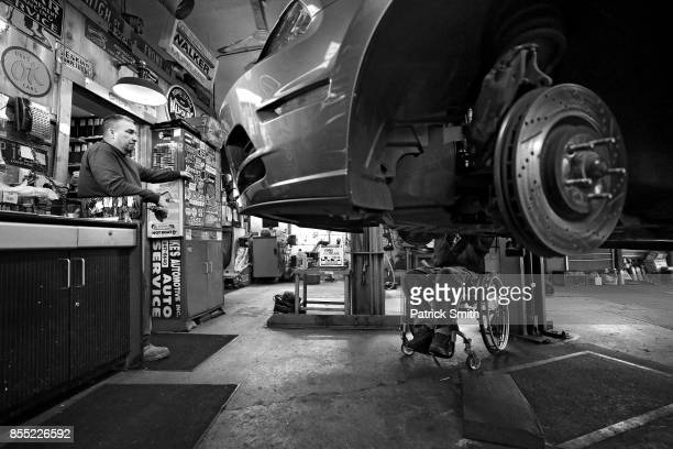 Pro Wheelchair Bodybuilder Johnny Quinn replaces brake pads on his Ford Mustang as owner Ike Rowland looks on at Ike's Automotive and Marine on April...