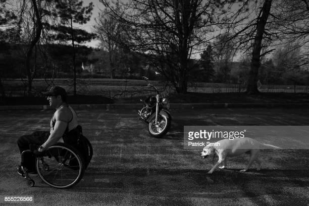 Pro Wheelchair Bodybuilder Johnny Quinn walks his dog Sage past a parked motorcycle at his home on April 14 2017 in Chesterbrook Pennsylvania Quinn...
