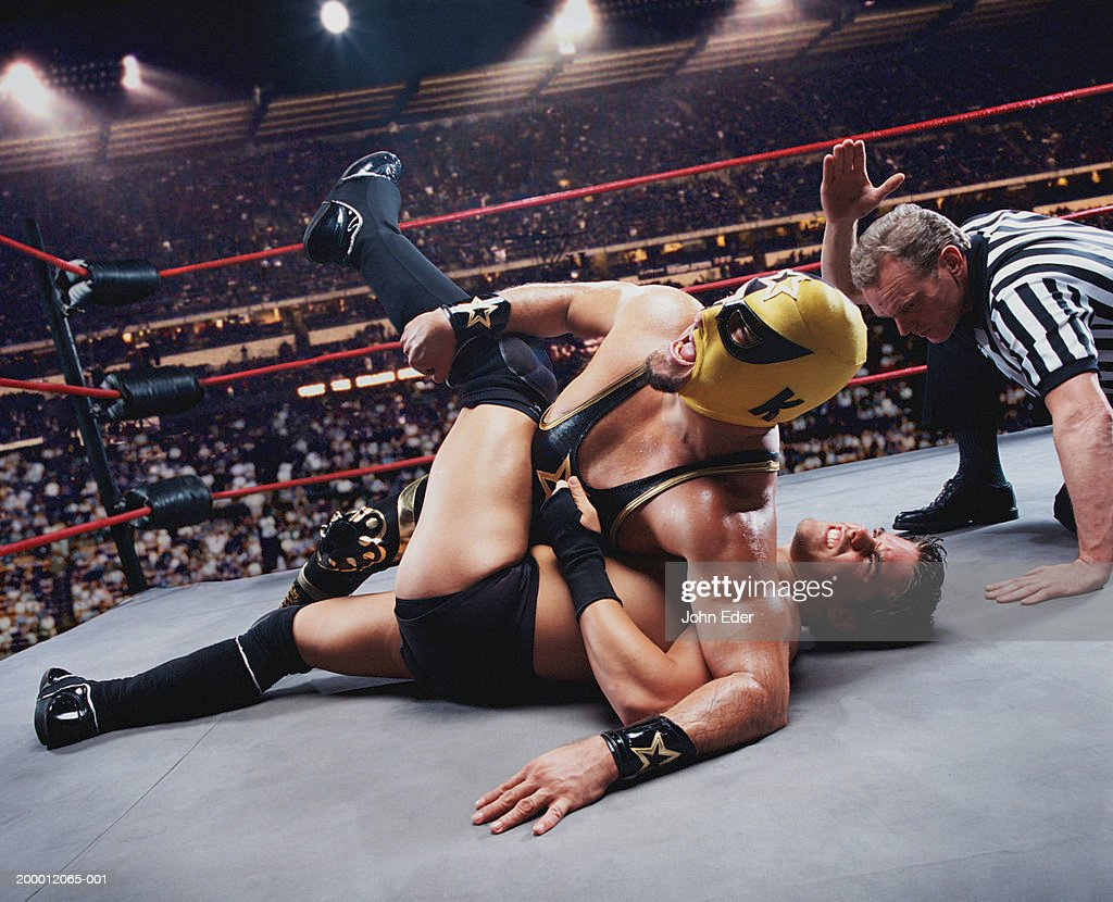 Pro wrestler pinning opponent on mat, referee counting down : Stock Photo