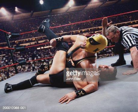 Pro wrestler pinning opponent on mat, referee counting down : Bildbanksbilder