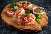 Proaciutto ham, Italian bruschetta appetizers with soft chees, onions, whole grain mustard, chillies and fresh rosmary