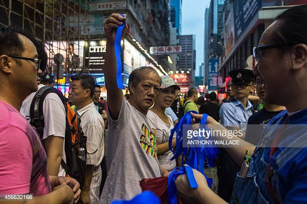 A proBeijing activist collects a blue ribbon as pro Hong Kong government speeches are made in the Kowloon district of Hong Kong on October 4 2014...