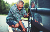 Man changing wheel after a car breakdown. Transportation, traveling concept