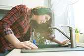 Serious concentrated young woman in checkered shirt checking faucet while having problem with dropping faucet in kitchen