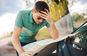 Bad navigation. Young man having a problem with orientation on the road during his journey with a car. He looking at map and try to find the missed road. Traveling and transportation concept