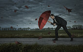 Crisis, trouble, problems concept. Businessman walks in the storm with copy space
